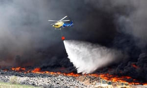 A helicopter throws water over the tyre dump fire.