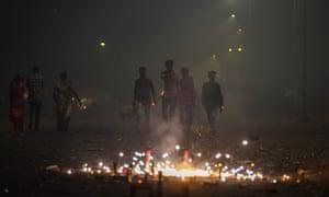 Indian men walk past fireworks amid smog on Diwali