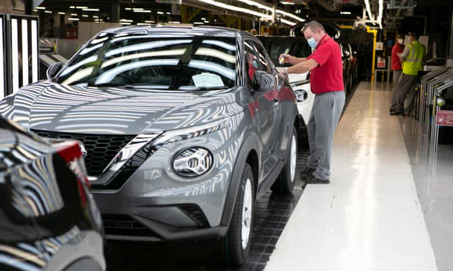 A shiny grey Nissan SUV on the production line, with a worker wearing a red shirt and a face mask inspecting it