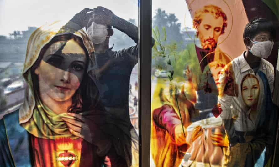Boys peep through the glass of a church in Gauhati, India, at Christmas. Harassment of Christians has increased in the country.