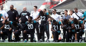 Jacksonville Jaguars players kneel in protest before their game against the Baltimore Ravens at Wembley Stadium in London on 24 September, the first NFL game of the day.