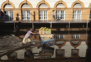 A man pushes a shopping cart loaded with bananas on a street flooded by the Negro River in downtown Manaus.