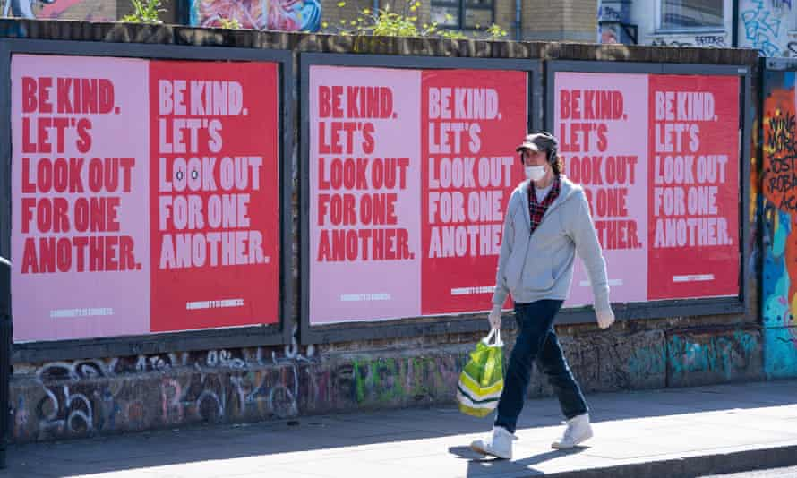 A man wearing a face mask passes a row of posters in Shoreditch, east London