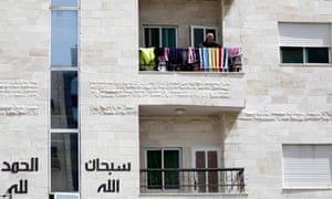 A man looks out of his balcony in Amman