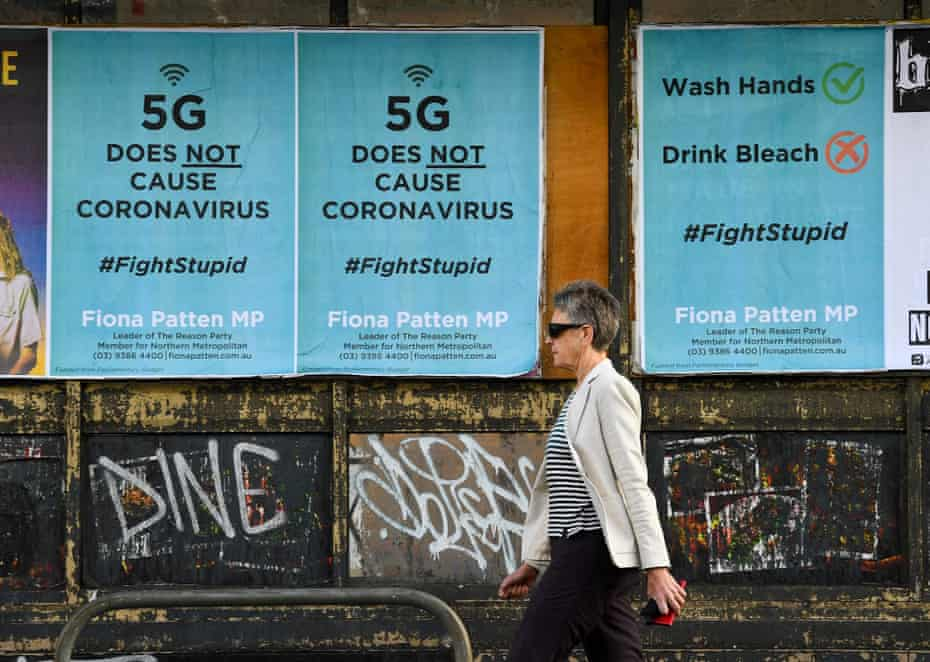 This file photo taken on June 24, 2020 shows a pedestrian walking past public service announcement posters in Melbourne amid the COVID-19 coronavirus pandemic, negating a conspiracy that 5G telecommunications technology causes the coronavirus.