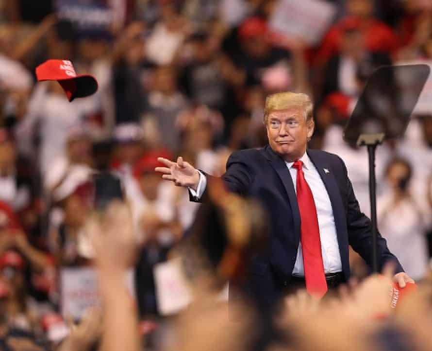 Donald Trump tosses a Maga cap into the crowd in Sunrise.