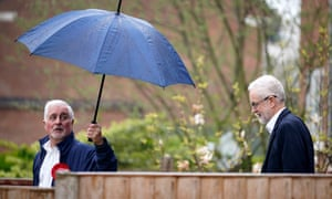 Man leans open umbrella towards Jeremy Corbyn