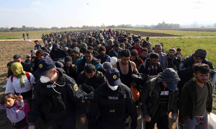 Migrants and refugees escorted by soldiers