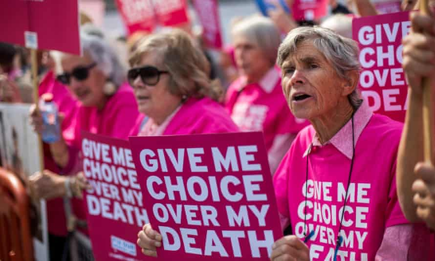 Campaigners for assisted dying hold signs reading 'Give me choice over my death'.
