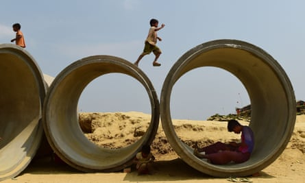 a rohingya child plays on top of concrete pipes in Bangladesh