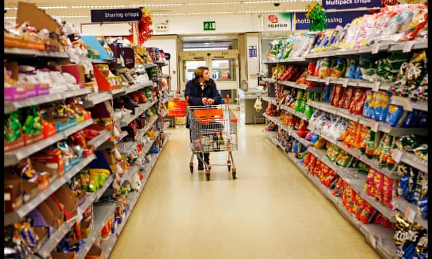 A shopper peruses the crisps on offer in a supermarket in Nottingham.