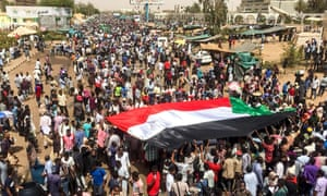 Demonstrators unfurl a national flag at a rally in front of the military headquarters in Khartoum on Wednesday.