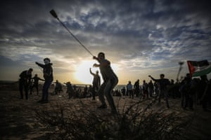 Gaza stripPalestinians throw stones with slingshots in response to Israeli forces' intervention with gas bombs during maritime protest against Israel's ongoing blockade of Gaza on the strips northern coast.