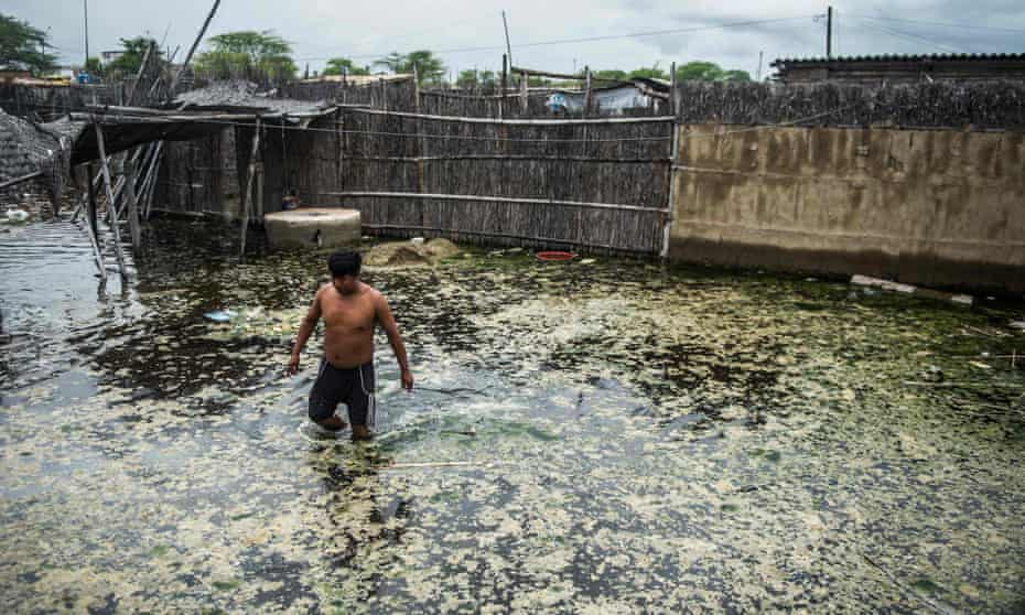 A local wades through muddy waters that have flooded the streets in La Union, northern Peru.