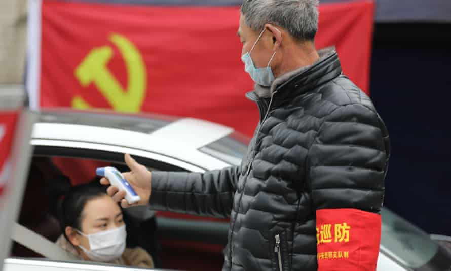 A volunteer checks the temperature of passersby at a checkpoint in Hangzhou in east China's Zhejiang province.
