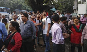 People stand outside their offices after rushing outdoors following tremors in Kolkata, India