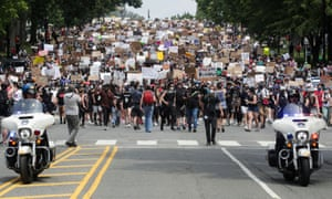 Demonstrators hold signs as they walk down Capitol Hill during a protest against racial inequality in the aftermath of the death in Minneapolis police custody of George Floyd, in Washington.