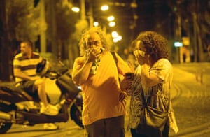 A couple cover their faces from tear gas   in Athens