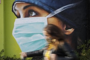A woman walks in from of a mural of a nurse in Milan.