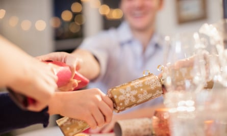 A family pulls Christmas crackers at the dinner table