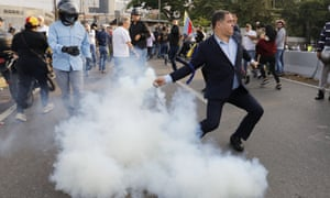 A Maduro opponent throws a tear gas canister back at military personnel guarding La Carlota air base.