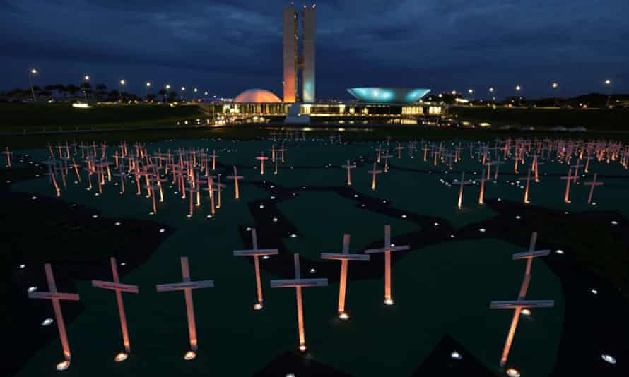 Crosses depicting people murdered for defending the forest stand on a large map of the Amazon, during a protest against the illegal timber trade, in front of the Brazilian National Congress building, in Brasilia, Brazil, 21 November 2017