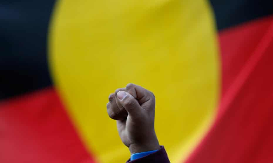 A raised fist in front of an Aboriginal flag