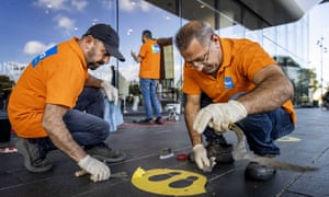 Employees remove Covid-19 social distancing safety stickers for the Stedelijk Museum in Amsterdam in The Netherlands as the 1.5 metre rule has ended.