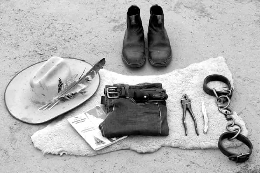A hat, jeans with belt and knife, a pair of plyers, pair of hobbles.