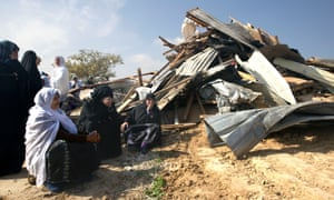 Bedouin women in the southern Israeli community of Umm al-Hiran sit outside a structure destroyed by police during an operation in which two people died including a policeman.
