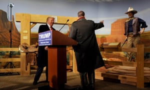 Donald Trump laughs as his Iowa state campaign director Chuck Laudner points at a mannequin of John Wayne at a museum in Iowa.