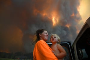 Sharnie Moran and her 18-month-old daughter, Charlotte, as thick smoke rises from bushfires near Nana Glen, near Coffs Harbour in November