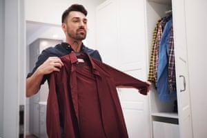 Man choosing shirt from wardrobe