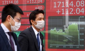 Electronic displays in Tokyo reflect stock market trends, as the financial world reacts to the Covid-19 pandemic.