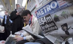 Metro newspaper reader on London tube train