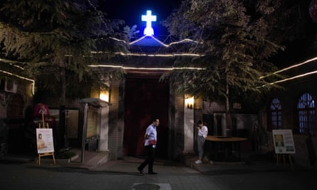 A man waits outside during a mass at the South Cathedral in Beijing