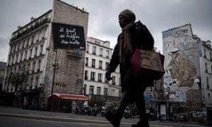 A woman walks down Rue de Belleville earlier in the coronavirus crisis.