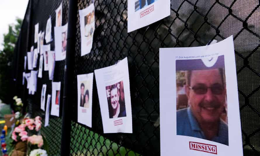 Pictures of missing people at a memorial as rescue personnel continue their search for victims.