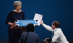 Theresa May is handed a fake P45 by the comedian Simon Brodkin during her speech at the Conservative party conference.
