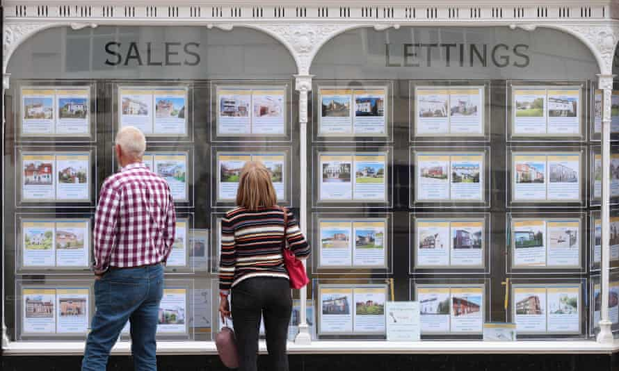 People looking at house price signs