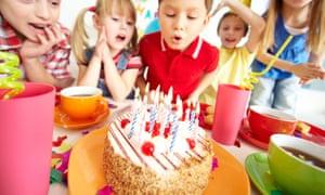 Children looking at birthday cake