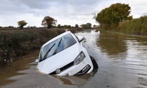 car tipped on its side in floodwater