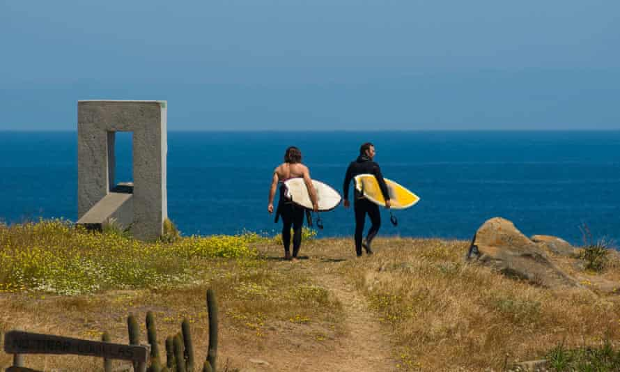 Two male surfers wearing wetsuits walking down a dirt path with surfboards to surf Punta de Lobos, Pichilemu, Chile.