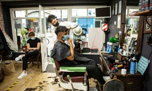 Dorian Zhilla cuts Shad Chowdhury's hair at the Barber of Seville shop in Brixton, south London, the day hairdressers were allowed to reopen following the easing of lockdown restrictions in England.