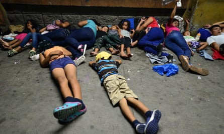 Honduran families sleep in the streets waiting to board a bus leaving the Metropolitan Center of San Pedro Sula, 300 kms north of Tegucigalpa, to travel to the Guatemala border on 9 April 2019.