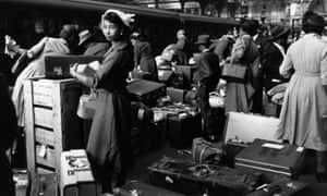 A woman waits with her luggage at Victoria in 1956