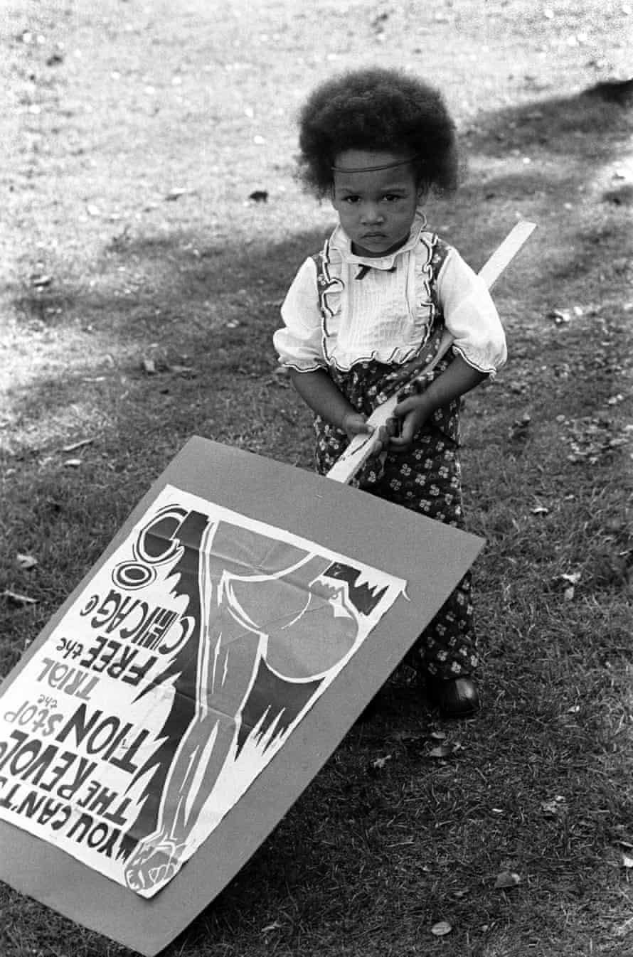 A girl holds a placard