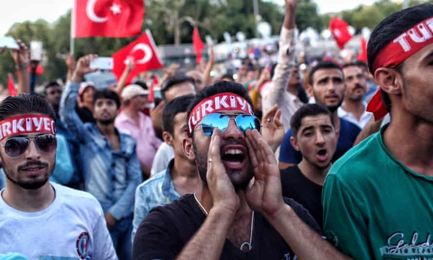 Supporters of Turkish president Recep Erdoğan chant slogans and wave Turkish flags as they gather in Istanbul's main Taksim Square.
