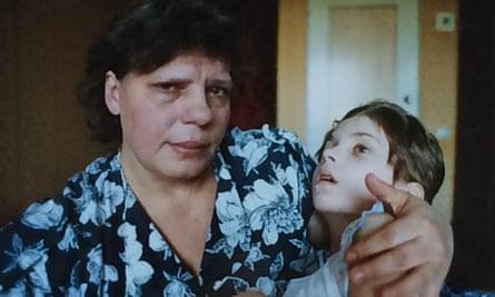 Oksana is held by a family member.