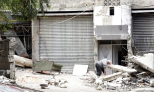 A man sifts through rubble after heavy fighting in Yarmouk in April.